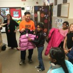 Vic passes out coats to the kids.