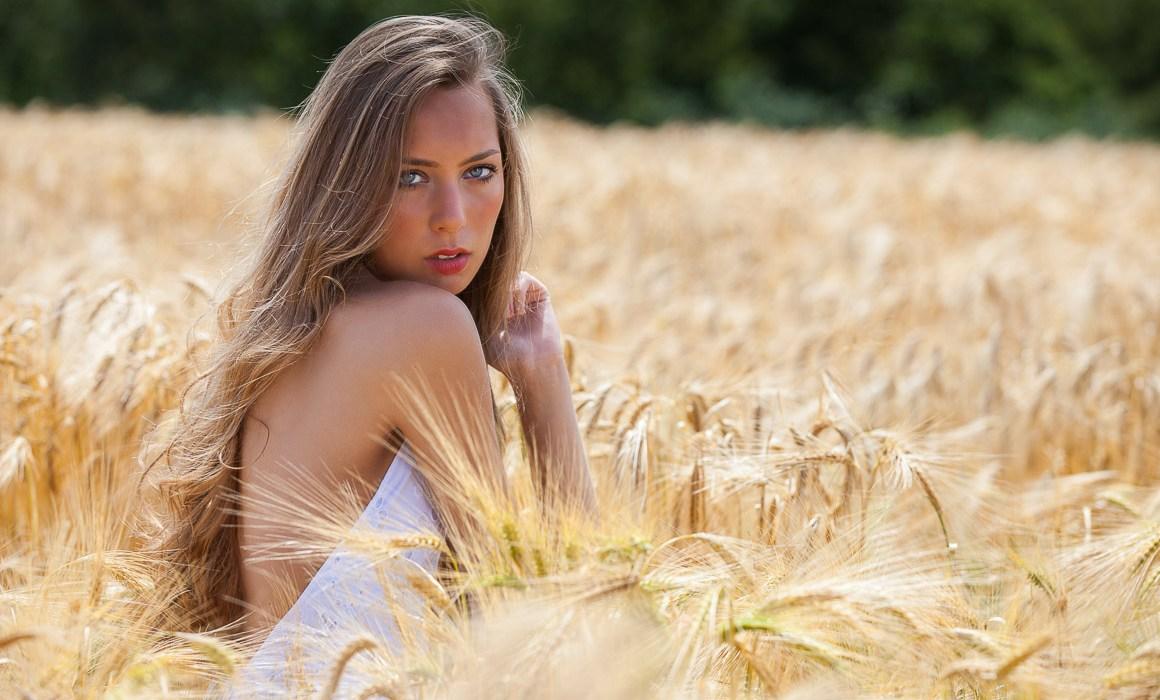 Jeune modèle dans un champs de blé en robe blanche