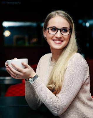 A blonde girl holding a cup of tea at Sprinkles Gelato in Winton, Bournemouth.