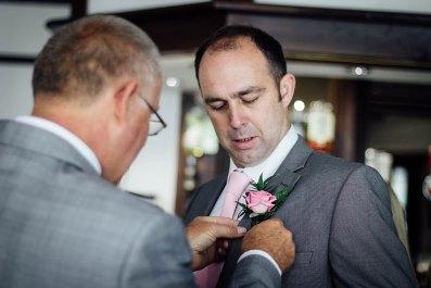 Best men pinning buttonholes