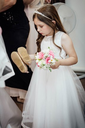 Young bridesmaid carrying her shoes