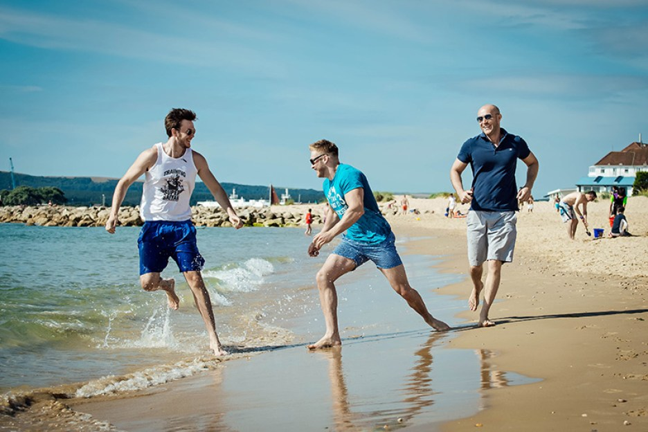 Portrait photograph of family members running along the beach