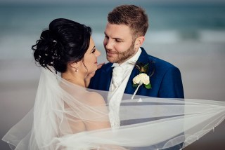 Bride and groom with veil blowing on Bournemouth beach