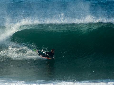 Bodyboarder skims swiftly across a Dee Why wall.