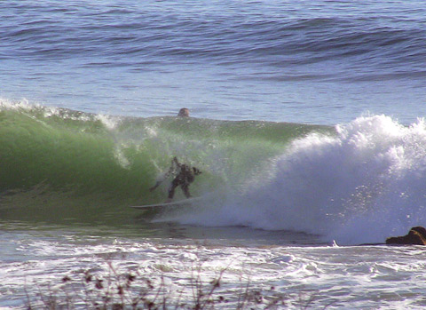 Getting a little cover before being crunched in front of the rocks at La Conchita, CA.