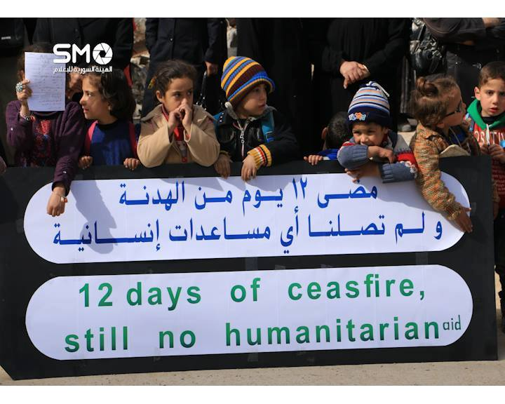 Children hold sign in Daraya protesting the lack of humanitarian aid, despite the ceasefire