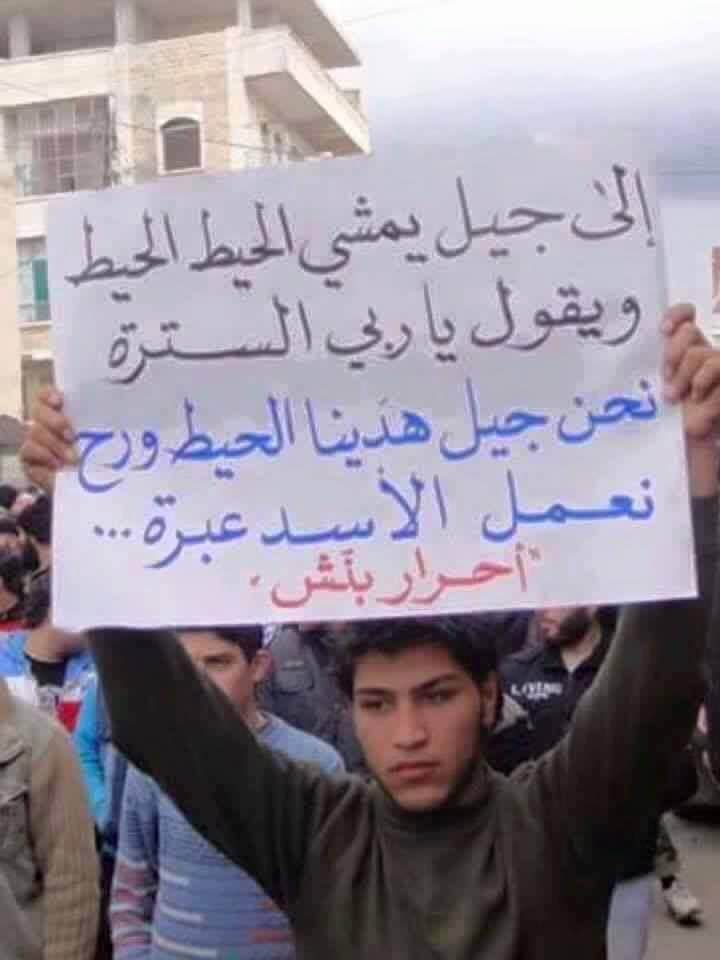 "Young protestor holds placard reading: ""To the generation who  lived in fear and spent their lives in caution. We are the generation that broke the walls of fear. We will make an example out of Assad"""