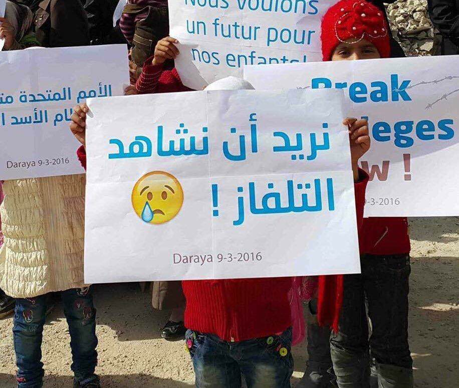 """Child in Daraya holds sign saying """"I want to watch TV!"""""""
