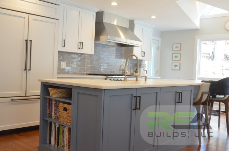 A finished kitchen project with quartz counter-tops, a blue island, and white cabinetry.