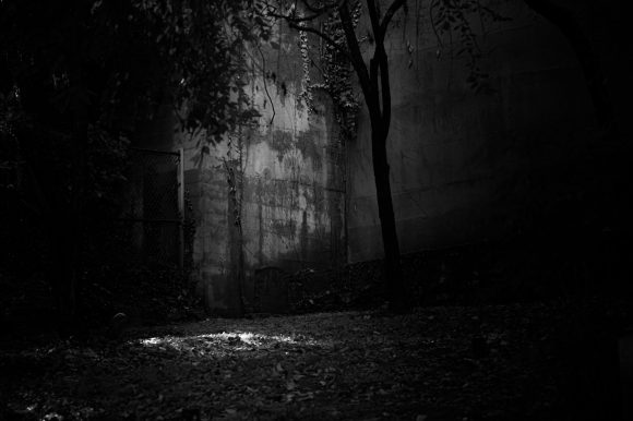 A lone grave stone in the middle of a dark space, with a wall behind it.
