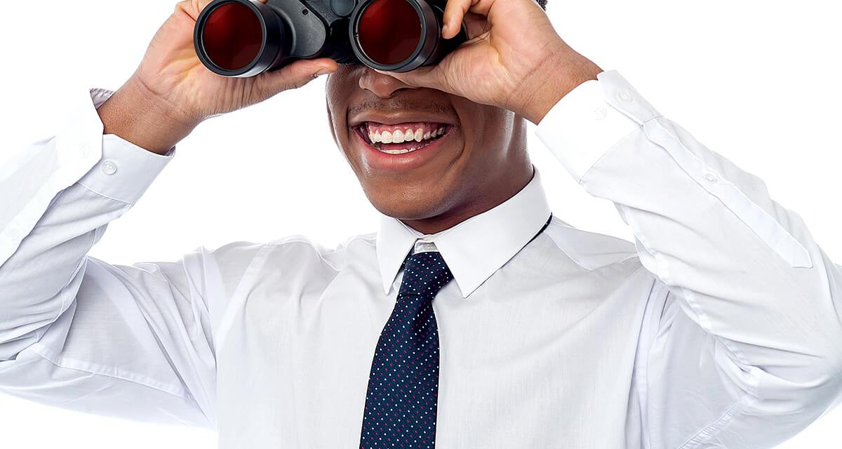 Business man in dress shirt and tie smiles and looks to the future through binoculars