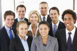 Group of male and female professionals standing together and smile at the camera