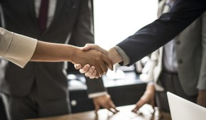 A woman and man in business attire shake hands