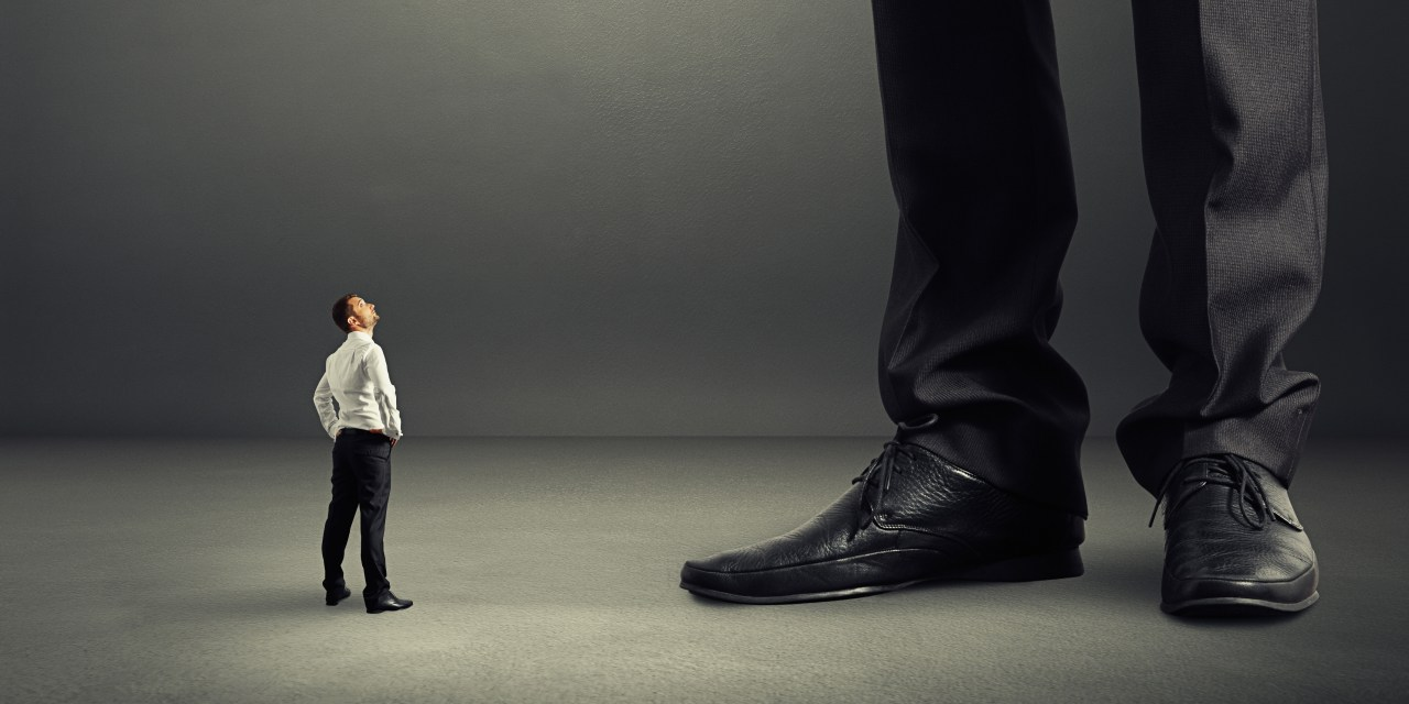 Tiny man in business attire cranes his neck to see up to a giant man, who is only visible to the knee