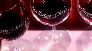 Closeup image of wine glasses etched with the William Chris Vineyards name, ful of red wine
