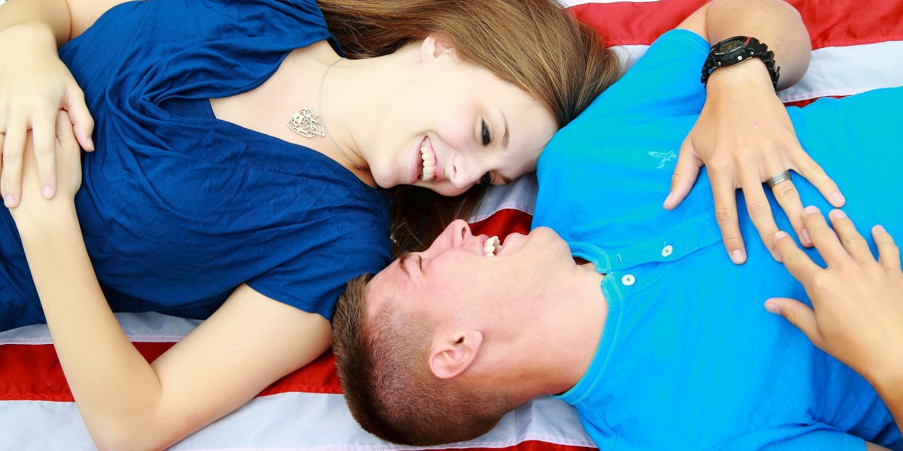 husband and wife lay on an American flag, talking and smiling