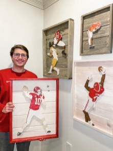 Nick Garrett with some of his favorite 3D woodcuttings of former Alabama players. (contributed)