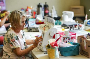 Peggy Plyler makes an adjustment to her sewing machine's settings using a touch screen. Today's sewing machines operate with software, motherboards and touch screens, with traditional needles, thread and bobbins. (Meg McKinney / Alabama NewsCenter)