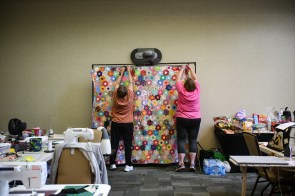 Quilters hang a hand-pieced Flower Garden quilt, made by Susan Hill Lee, right, and assisted by Cheryl Clabough, left. A rotation of quilts were displayed at the retreat for inspiration. (Meg McKinney / Alabama NewsCenter)