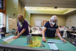 Larry Cartwright, left, and Susan Wagner measure and cut fabric strips using rotary cutters and acrylic rulers, tools that make measuring and cutting fabrics accurate. (Meg McKinney / Alabama NewsCenter)