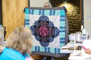 As each section of a quilt was completed, quilters, like Susan Wagner, held them up for all to see. (Meg McKinney / Alabama NewsCenter)