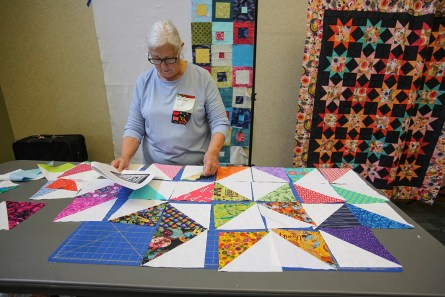 Concentrating on the layout of her Friendship quilt blocks, Marie Guess checks the placement of blocks. The Friendship quilt blocks were traded at the retreat. (Meg McKinney / Alabama NewsCenter)
