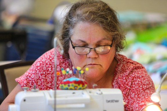 With fabrics reflected in her glasses, Kimmie Monteabaro concentrates on sewing blocks together during the retreat. (Meg McKinney / Alabama NewsCenter)