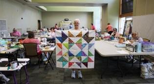 Marie Guess completed her Friendship quilt top during the retreat, made with traded blocks from other retreaters. (Meg McKinney / Alabama NewsCenter)