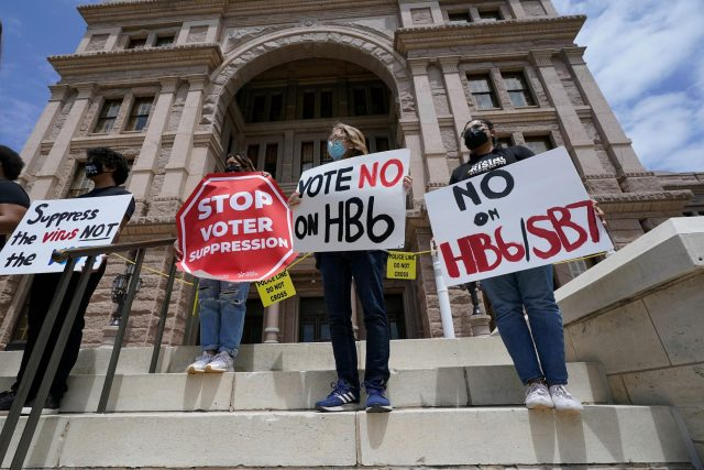 People opposed to Texas voter bills HB6 and SB7 hold signs during a news conference hosted by Texas Rising Action on the steps of the State Capitol in Austin