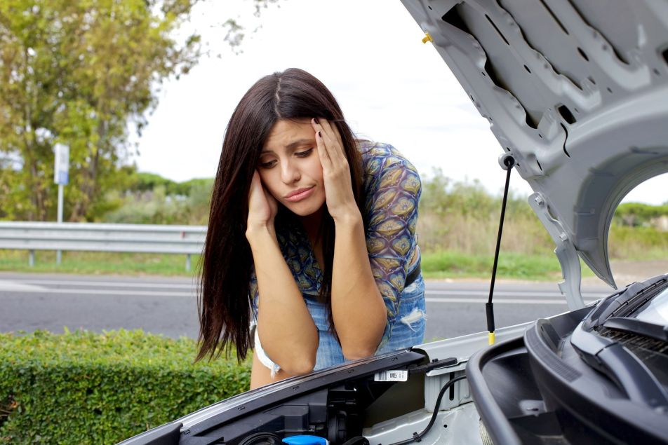 woman looking at engine of broken-down car