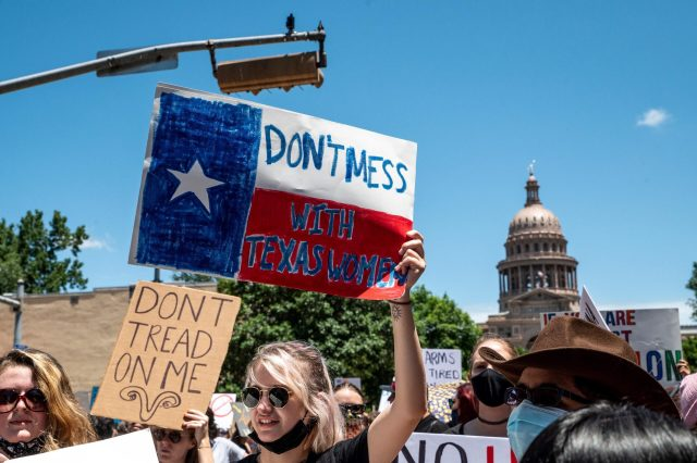 A federal judge Friday questioned Texas abortion ban's controversial enforcement mechanism. Abortion protesters hold up signs outside the Texas state capitol on May 29