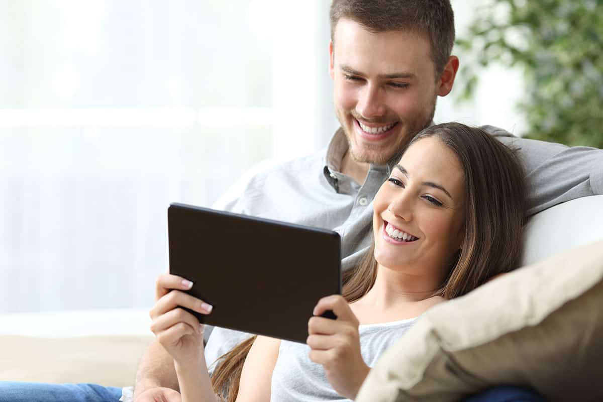 A newly-engaged couple planning their wedding using online RSVP services