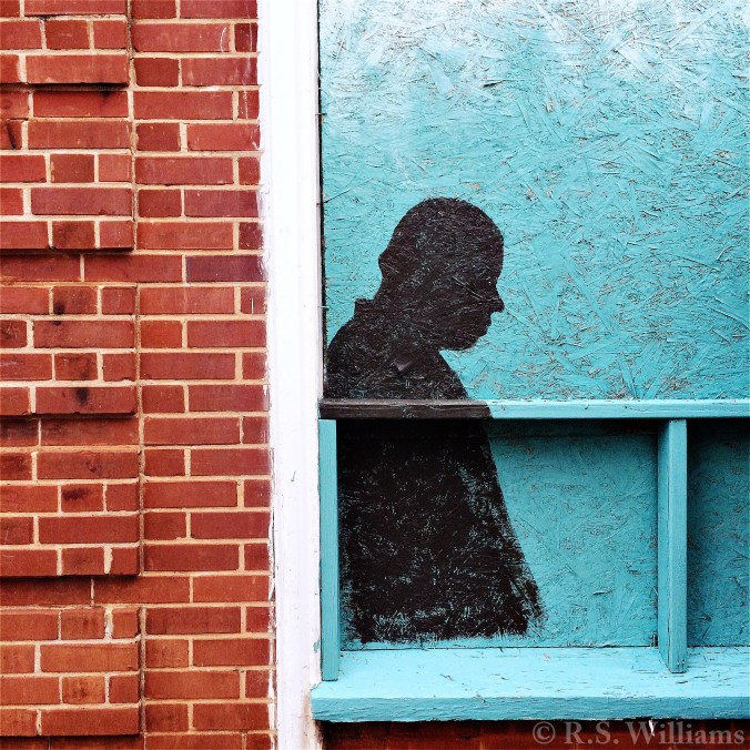 Close view of brick building facade and boarded-up corner of shop window. Plywood and 2x4 windowsill are spray-painted turquoise, with a black silhouette (in profile) of a man's head and upper torso.