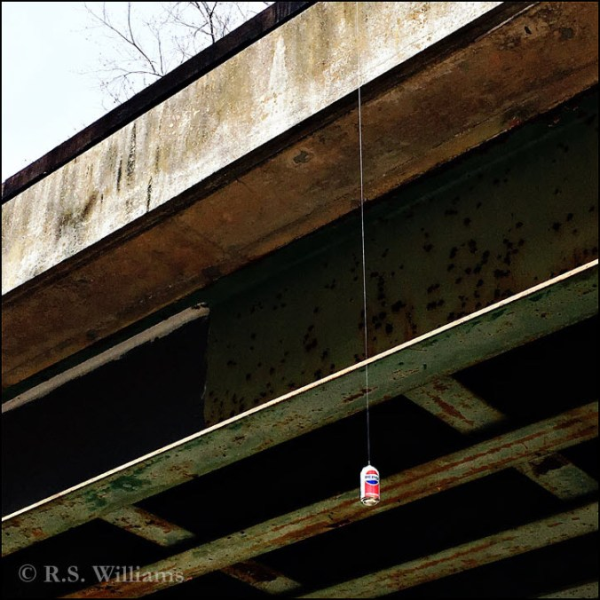 On a gray, overcast day, we look up into the green-painted, rusty steel beams under a railroad bridge, and also see the mossy concrete edge of bridge showing in the upper left corner of photo. Hanging from a thin piece of plastic fishing line is a 12-ounce Pepsi-Cola can bearing the bright red-white-and-blue standard Pepsi can design and logo. Presumably, the fishing line tied to the can is affixed somewhere on top of the railroad bridge, off camera.