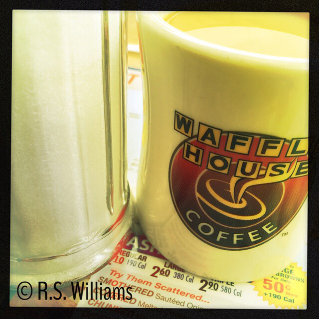 Closeup, vivid color photo of a clear glass sugar dispenser next to a cream-colored ceramic Waffle House logo mug. Both sit on a laminated Waffle House menu, the Hashbrowns section of which is included in the lower middle portion of the image (