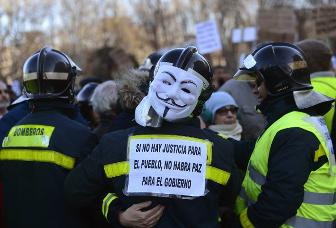 "A firefighter wearing a Guy Fawkes mask and holding a placard reading ""If there is no justice for the people, there will be no peace for the government"" attends a demonstration on February 23, 2013 in Madrid. (AFP Photo / Pierre-Pholippe Marcou)"