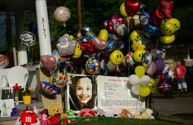 An FBI person missing sign stands in front of the family house of Gina DeJesus, one of the three women which were held captive for a decade, as it is decorated by well wishers May 7, 2013 in Cleveland. (AFP Photo / Emmanuel Dunand)
