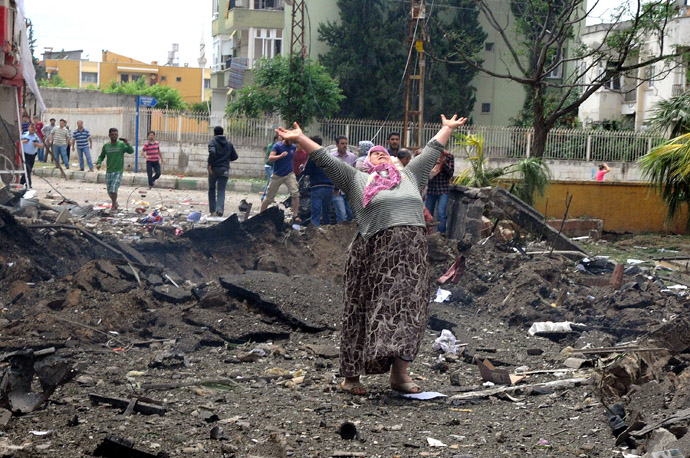 A woman raises her arms and shouts as she stands on the site where car bombs exploded on May 11, 2013 near the town hall in Reyhanli, just a few kilometres from the main border crossing into Syria (AFP Photo/IHLAS NEWS AGENCY)