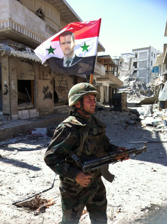 A Syrian army's soldier walks in a street left in ruins with a national flag featuring Syria's President Bachar al-Assad on June 5, 2013 in the city of Qusayr in Syria's central Homs province (AFP Photo / Str)
