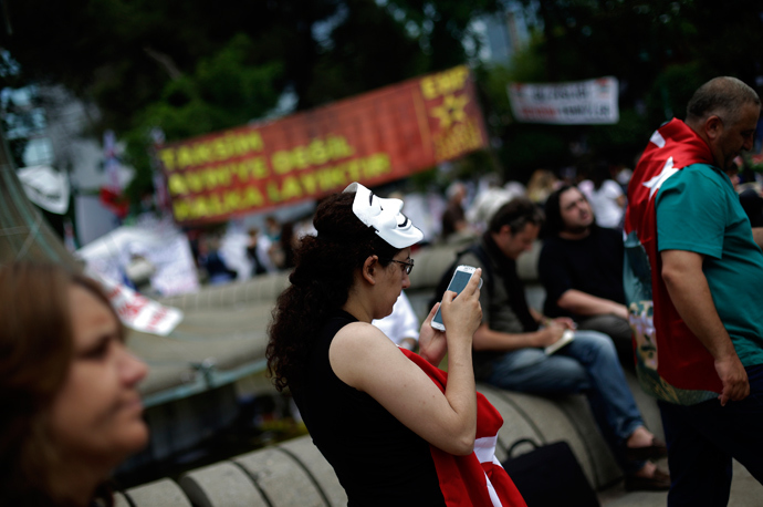 A protester uses her mobile device as she walks at Gezi Park on Taksim Square in Istanbul (Reuters / Stoyan Nenov)