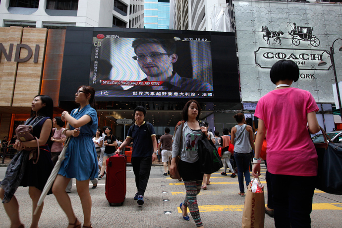 People cross a street in front of a monitor showing file footage of Edward Snowden, a former contractor for the U.S. National Security Agency (NSA), with a news tag (L) saying he has left Hong Kong, outside a shopping mall in Hong Kong (Reuters / Bobby Yip)