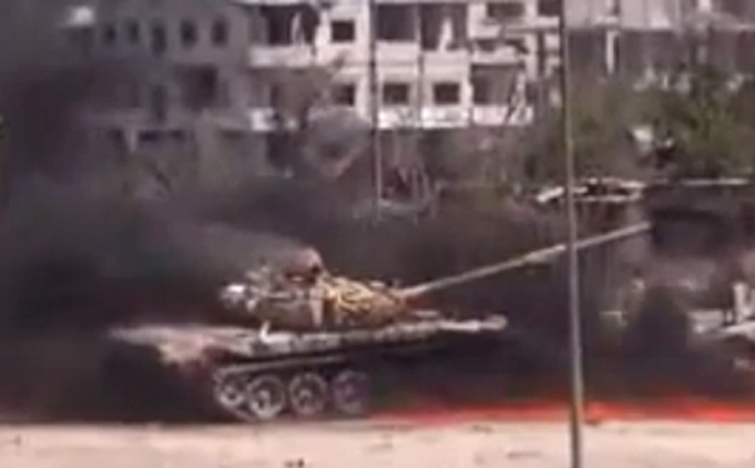 An image grab taken from a video uploaded on YouTube on August 27, 2013 allegedly shows smoke billowing from a Syrian government forces' tank at it was hit by an explosion in a Damascus' suburb (AFP Photo / Youtube)