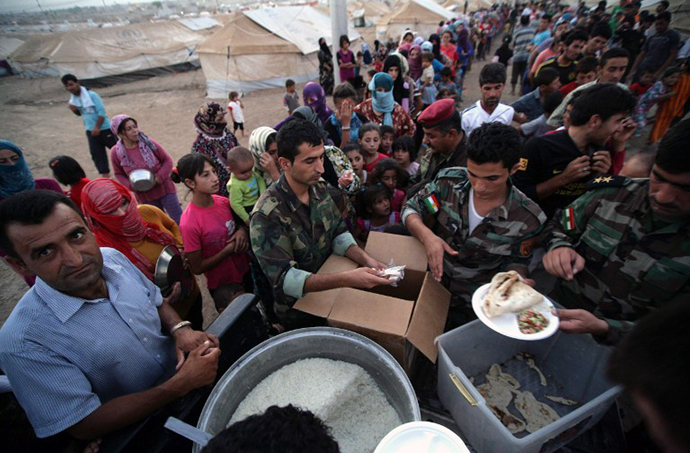 Syrian-Kurdish refugee families queue to get food at the Quru Gusik refugee camp, 20 kilometres east of Arbil, the capital of the autonomous Kurdish region of northern Iraq, on August 27, 2013. (AFP Photo / Safin Hamed)