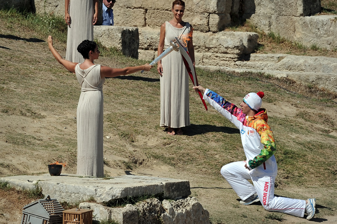 Greek actress Ino Menegakie acting as the priestesses passes the flame to the first torch bearer, Greek skier Giannis Anoniou, at the Temple of Hera on September 29, 2013 during the lighting ceremony in ancient Olympia (AFP Photo / Louisa Gouliamaki)