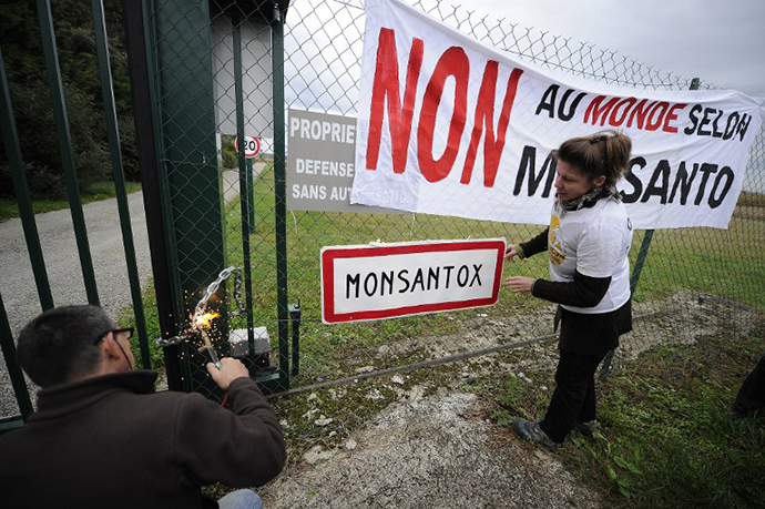 "Anti-GMO (genetically modified foods) protestors put a chain at the site entrance of US seed company Monsanto on October 12, 2013 during a day of action against the company, in Monbequi, southern France. Banner (R) reads: ""No to a world according to Monsanto"". (AFP Photo / Pascal Pavani)"