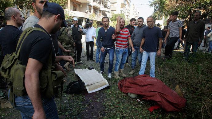 Army soldiers, security police officers and civilians gather around a body at the site of explosions near the Iranian embassy in Beirut November 19, 2013.(Reuters / Mahmoud Kheir)