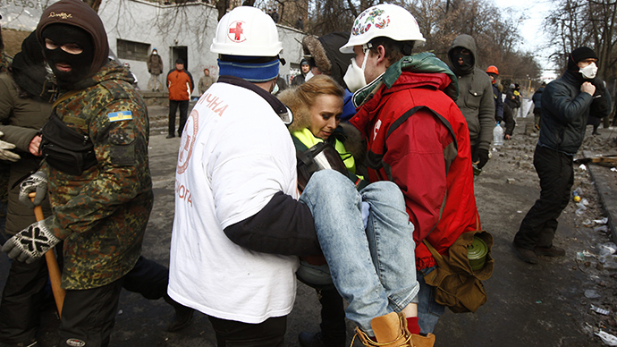 Medical volunteers carry a wounded journalist at the site of clashes with riot police in Kiev January 20, 2014. (Reuters / Vasily Fedosenko)