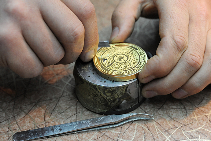 Producing souvenir Olympic medals with fragments from the meteorite in Chelyabinsk at the MAOK art workshop in Zlatoust. (RIA Novosti / Aleksandr Kondratuk)