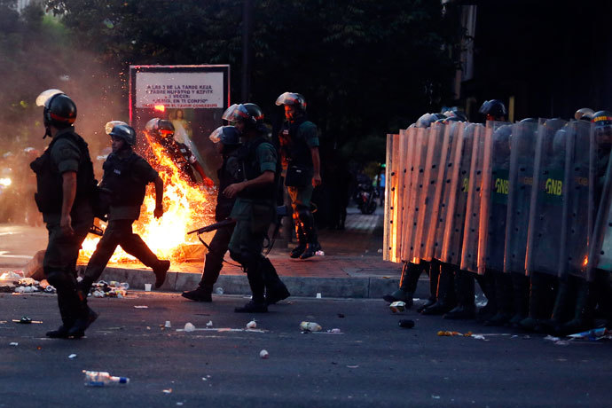 Riot police walk past a barricade of burning garbage during a protest against Venezuela's President Nicolas Maduro's government in Caracas February 12, 2014. (Reuters / Carlos Garcia Rawlins)
