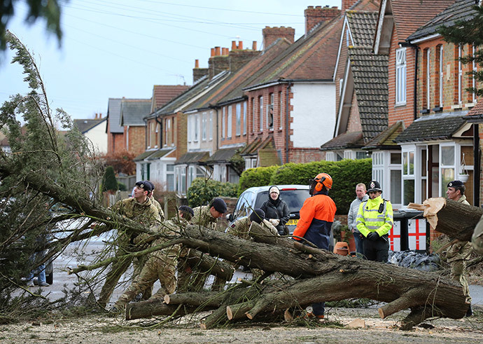 Members of the Army move a tree which was blown down in a flooded street in Egham, southern England, February 15, 2014. (Reuters / Paul Hackett)